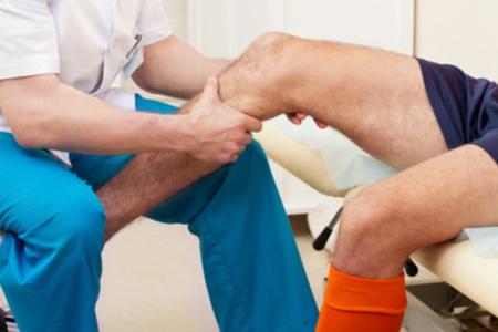 врач делает массаж колена