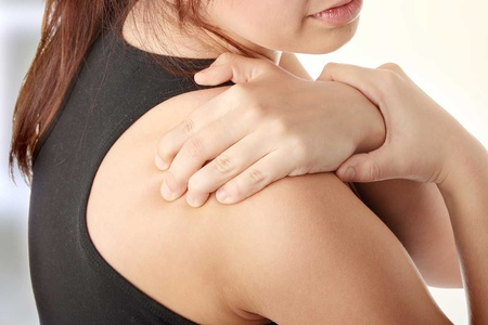 женщина держится за плечо
