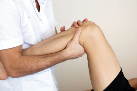 врач держит колено