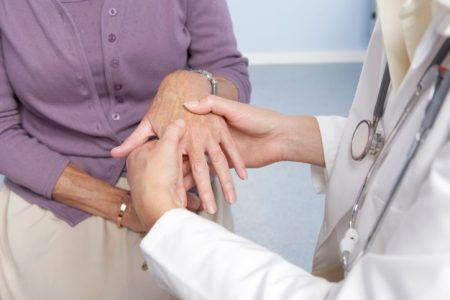 врач смотрит руку